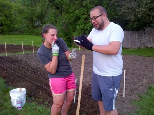 Sam and Rob racing to open pea packages for Bed 5, which Norma, Colleen, Sheryl, Chris, & Cindy earlier prepped for planting