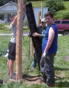 An AmeriCorps VISTA-led international team from the City of Montpelier's Parks Department steadies and levels fence posts