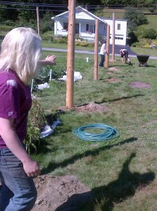 AmeriCorps VISTA volunteer Steph Olsen guides an international team to stabilize and level very large cedar fence posts
