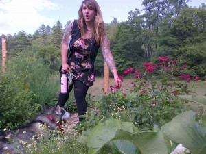 Herbalist indicates echinacea flowers growing beside bee balm while a husky dog rests at her feet