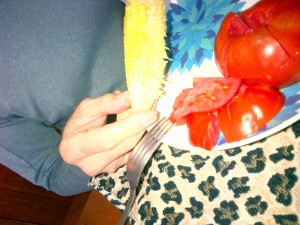 Someone eating an ear of corn and fresh sliced tomatoes on a plate