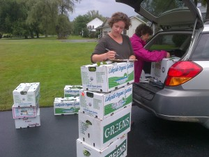 Allison and Karen weigh and record each box of food.