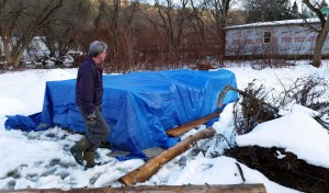 Chris weighs down the tarp covering the lasagna compost for the winter